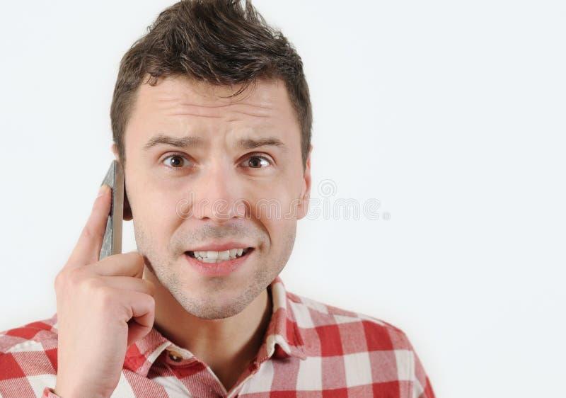 Hombre sorprendido que habla en su teléfono móvil y que mira la cámara imágenes de archivo libres de regalías