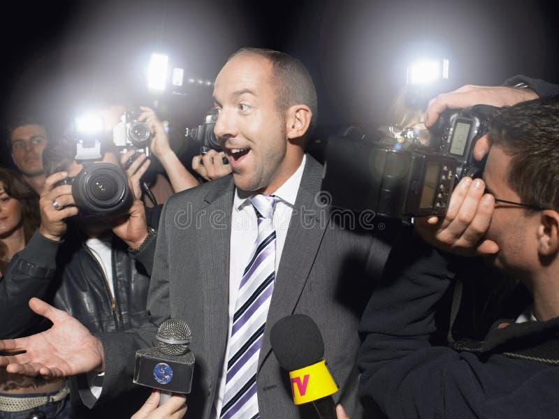 Hombre sorprendido rodeado por los paparazzis imagenes de archivo