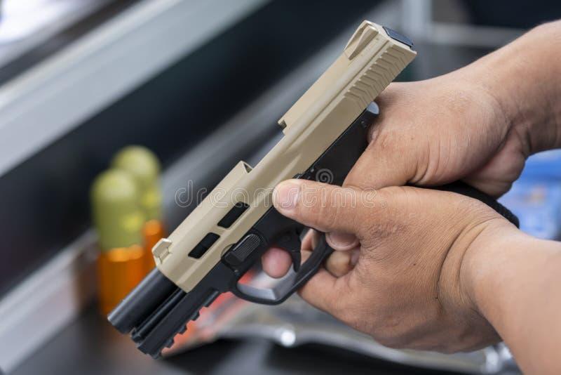 Hombre sostiene una pistola apuntando a una pistola lista lista para disparar fotografía de archivo libre de regalías