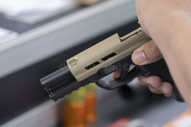 Hombre sostiene una pistola apuntando a una pistola lista lista para disparar foto de archivo