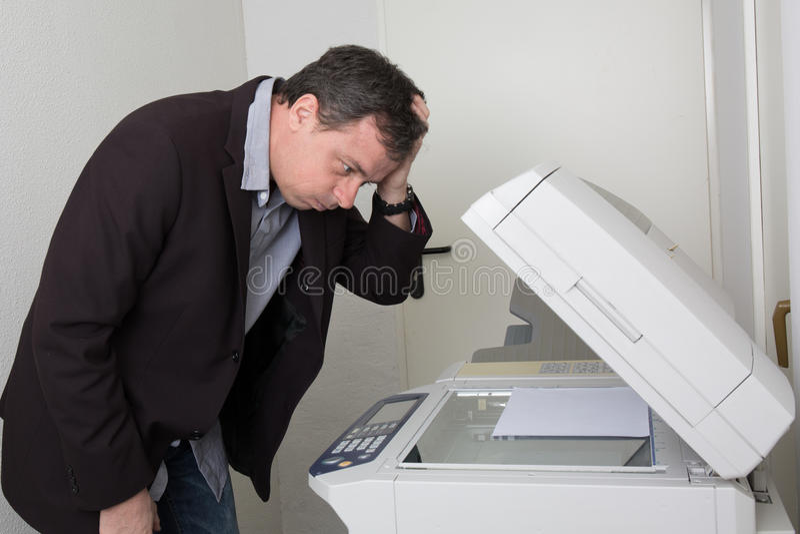 Hombre subrayado delante de una máquina de la copia foto de archivo libre de regalías