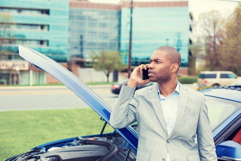 Hombre subrayado que tiene problema con la capilla quebrada de la abertura del coche que pide ayuda en el teléfono celular fotografía de archivo