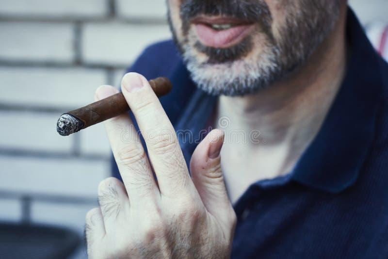 Hombre succusful barbudo que enfría y que fuma el cigarro precioso imagen de archivo