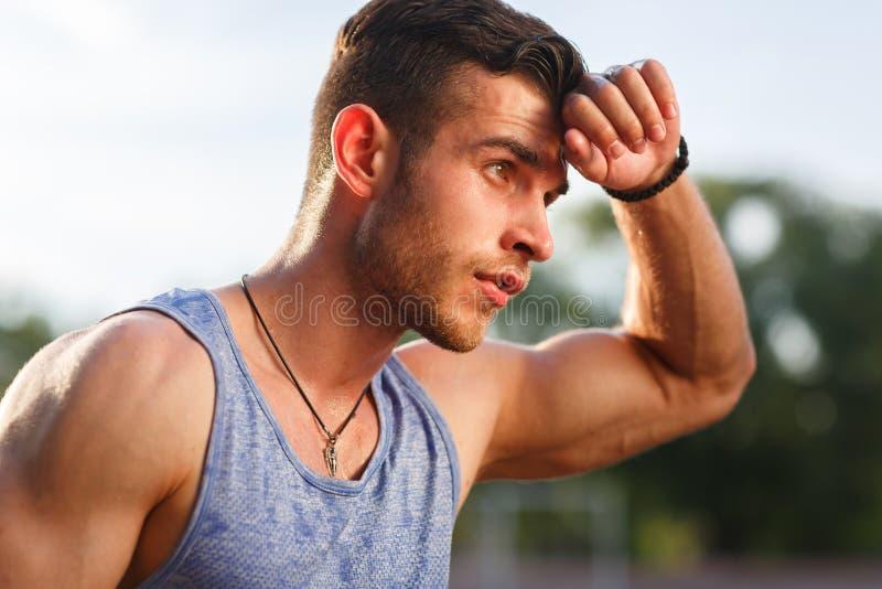 Hombre sudoroso muscular joven después del entrenamiento afuera el día soleado foto de archivo libre de regalías