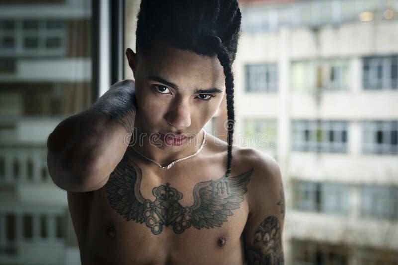 Hombre tattoed exótico hermoso que mira a la cámara descamisada imagen de archivo