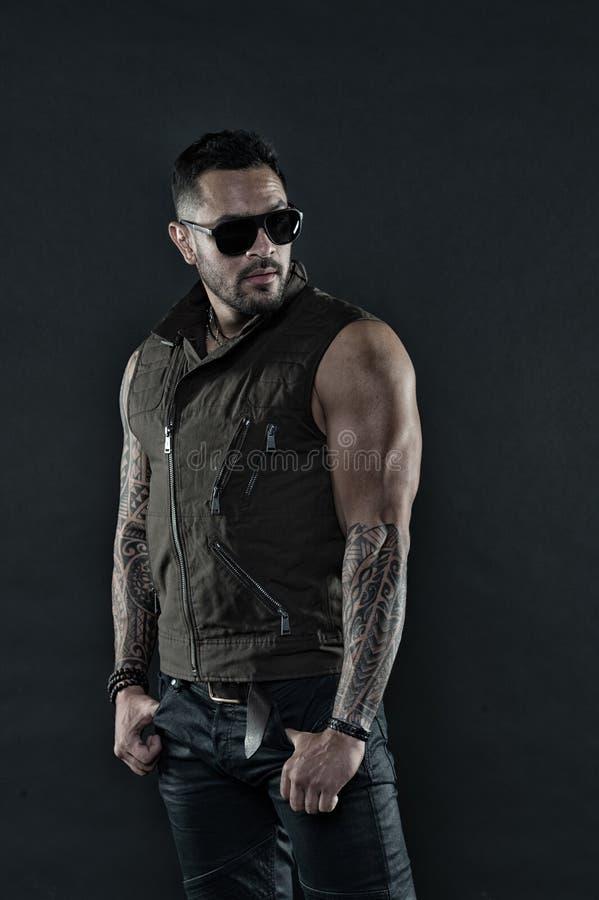 Hombre tatuado con el bíceps y el tríceps Modelo del tatuaje con la barba en cara sin afeitar El hombre barbudo con el tatuaje en imagenes de archivo