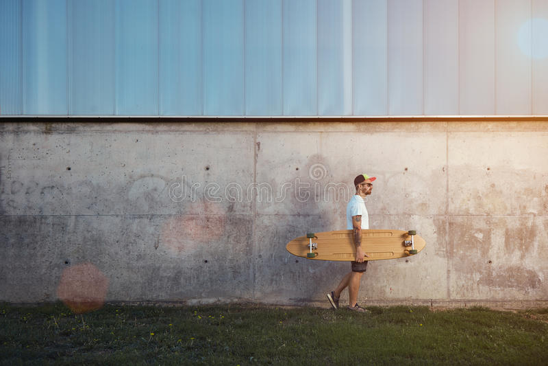 Hombre tatuado con longboard al lado de un muro de cemento imagen de archivo