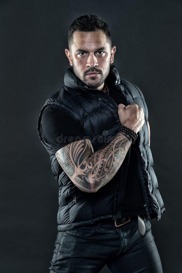 Hombre tatuado en ropa de moda Hombre con el tatuaje en piel del brazo fuerte Machista de la moda con confianza y carisma tatuaje imagen de archivo