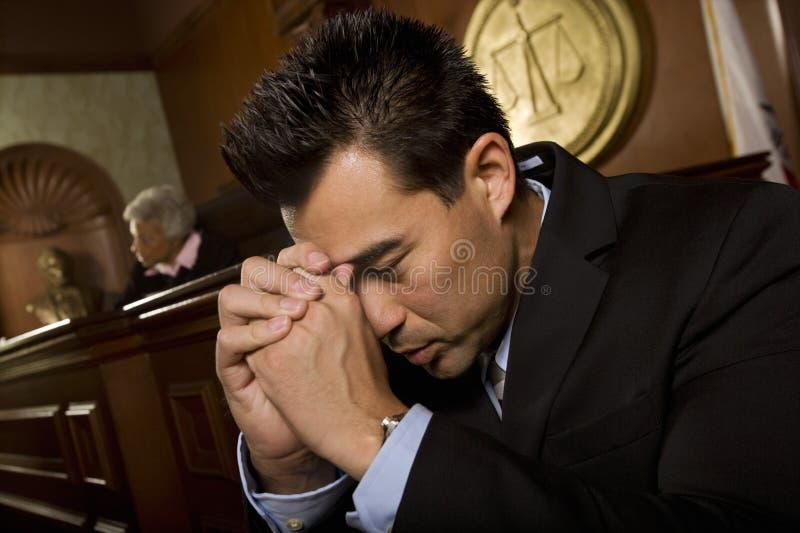 Hombre tensado que se sienta en sala de tribunal fotos de archivo