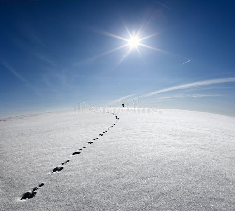 Hombre, tierra, universo Hombre solo que camina en campo de la corteza de la nieve en el rastro de liebres en el fondo de The Sun imagen de archivo