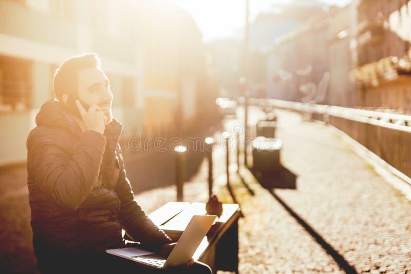 Hombre, tomando llamadas de teléfono y trabajando del callejón urbano durante otoño imágenes de archivo libres de regalías