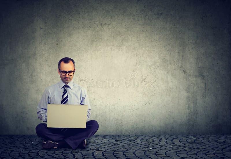 Hombre trabajador que usa el ordenador portátil en gris fotografía de archivo
