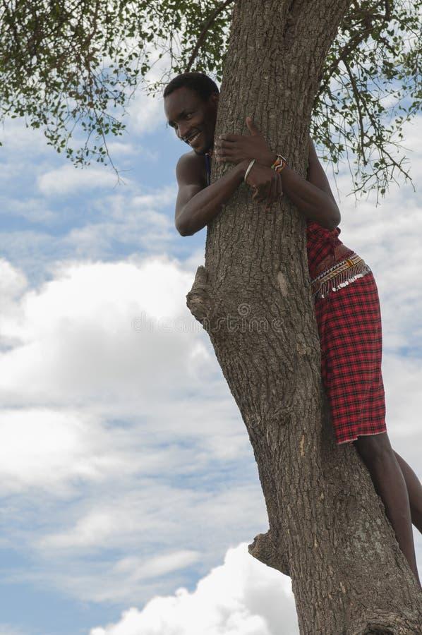 Hombre tradicional del Masai, árbol que sube que se divierte, y llevando el equipo rojo tradicional fotografía de archivo