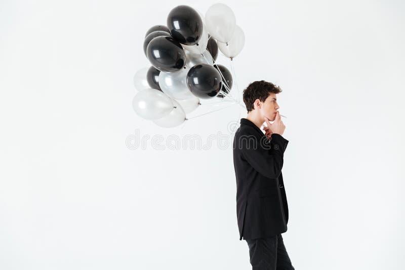 Hombre tranquilo que sostiene los balones de aire y que fuma el cigarrillo imagen de archivo libre de regalías
