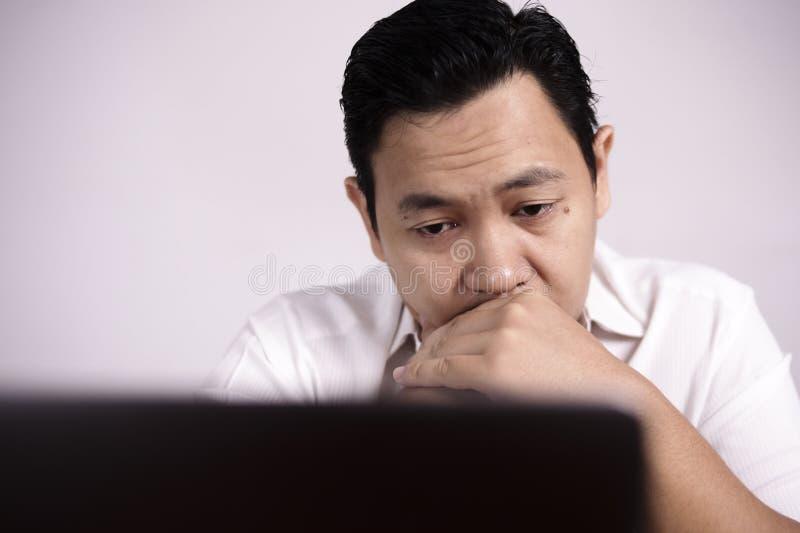 Hombre trastornado cansado que trabaja en el ordenador portátil, mala emoción negativa fotografía de archivo