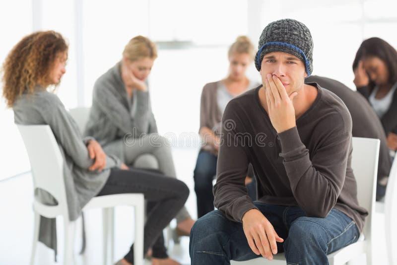 Hombre trastornado en el grupo de la rehabilitación que mira la cámara fotos de archivo