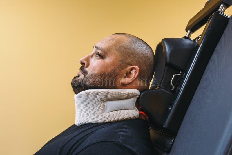 Hombre triste con el apoyo de cuello en el tratamiento físico de la recuperación en clínica con el equipo médico especial de la m fotografía de archivo libre de regalías