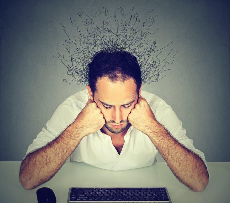 Hombre triste con el cerebro que derrite en las líneas que miran el teclado de ordenador fotografía de archivo