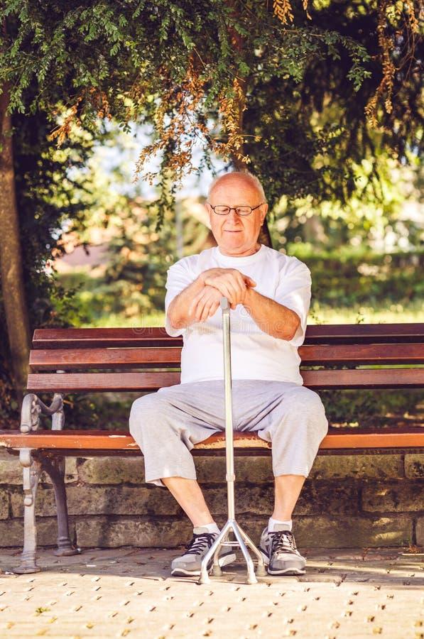Hombre triste del pensionista con su bastón que se sienta en banco foto de archivo libre de regalías