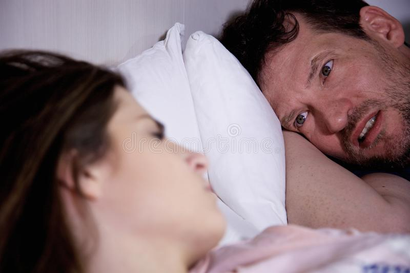 Hombre triste en la cama que mira dormir de la novia imagenes de archivo