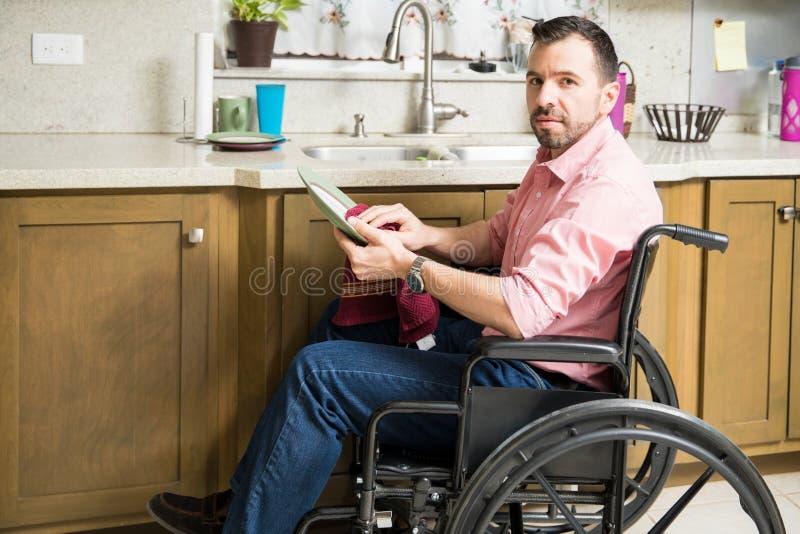 Hombre triste en platos que se lavan de la silla de ruedas fotos de archivo libres de regalías