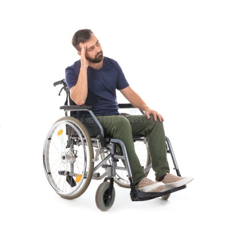 Hombre triste en silla de ruedas en el fondo blanco imágenes de archivo libres de regalías