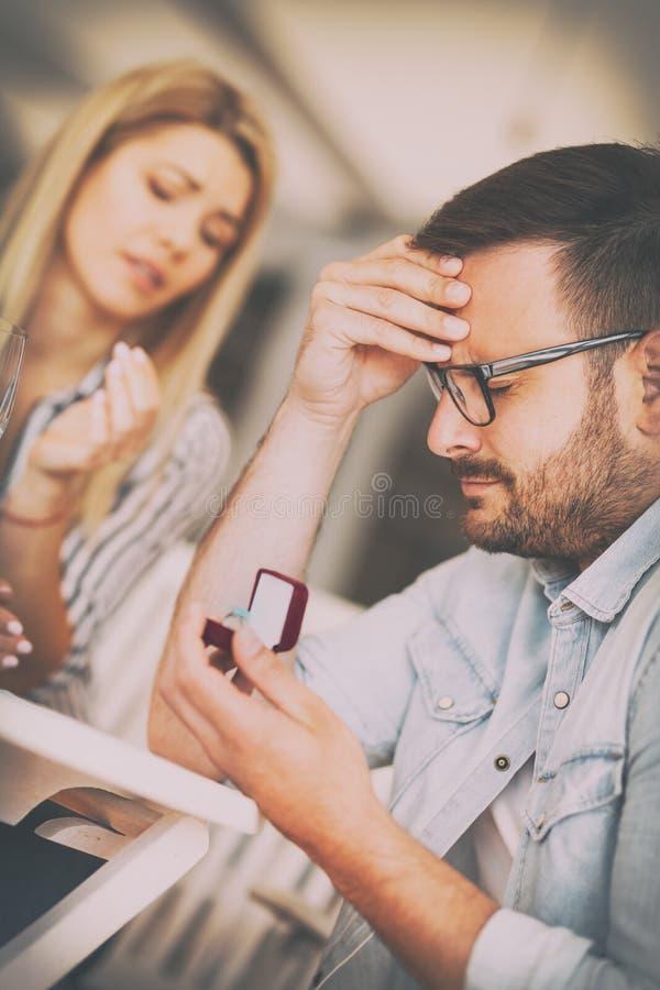 Hombre triste frustrado jóvenes que celebra casarse el anillo de compromiso, rechazo de la oferta fotografía de archivo libre de regalías