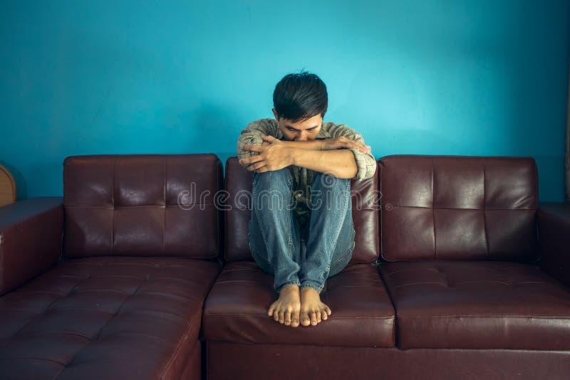 Hombre triste que se sienta en el sofá en sitio oscuro imágenes de archivo libres de regalías