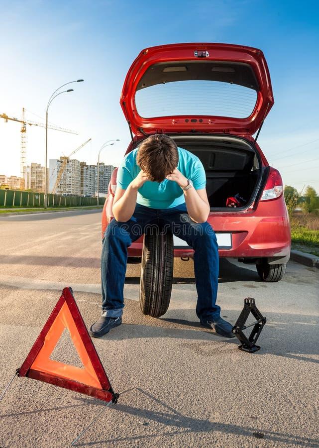 Hombre triste que se sienta en la rueda de repuesto cerca del coche quebrado imagenes de archivo