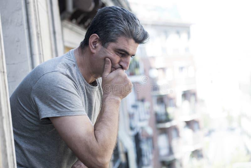 Hombre triste y deprimido 40s que mira con balco del aire libre en casa fotografía de archivo libre de regalías