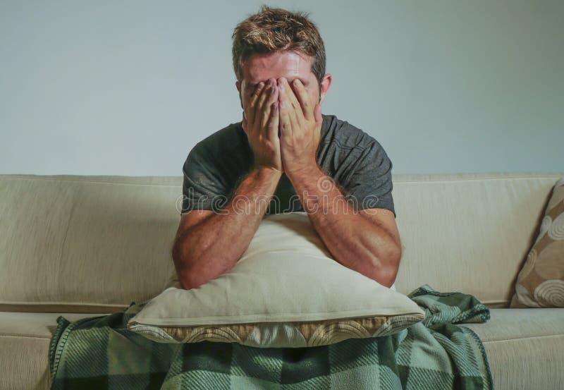 Hombre triste y desesperado joven en casa que se sienta en la cara de la cubierta del sofá del sofá con la depresión de las manos imágenes de archivo libres de regalías