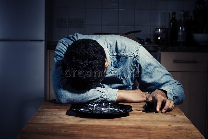 Hombre triste y solo que bebe después de cena fotos de archivo