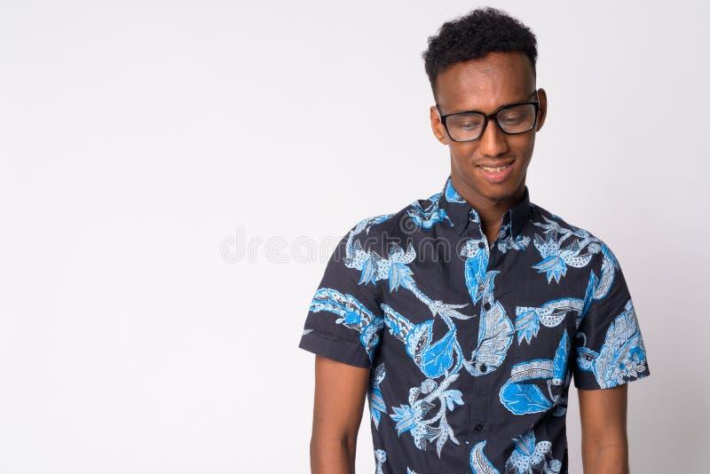 Hombre turístico africano feliz joven con las lentes que piensa y que mira abajo fotografía de archivo libre de regalías