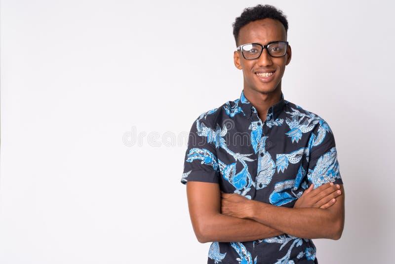 Hombre turístico africano feliz joven con las lentes que sonríe y que cruza los brazos fotografía de archivo libre de regalías