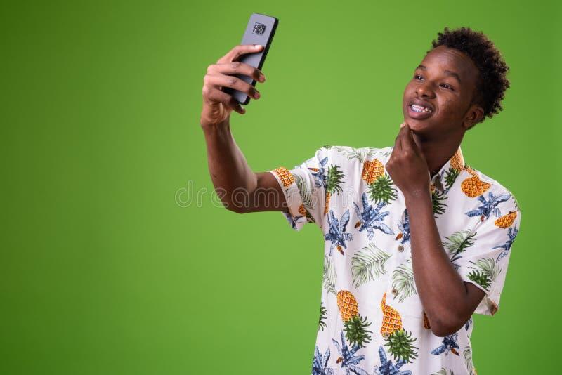Hombre turístico africano joven listo para las vacaciones contra backg verde foto de archivo