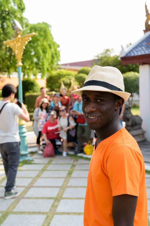 Hombre turístico africano negro joven que visita el templo budista en Bangkok fotografía de archivo