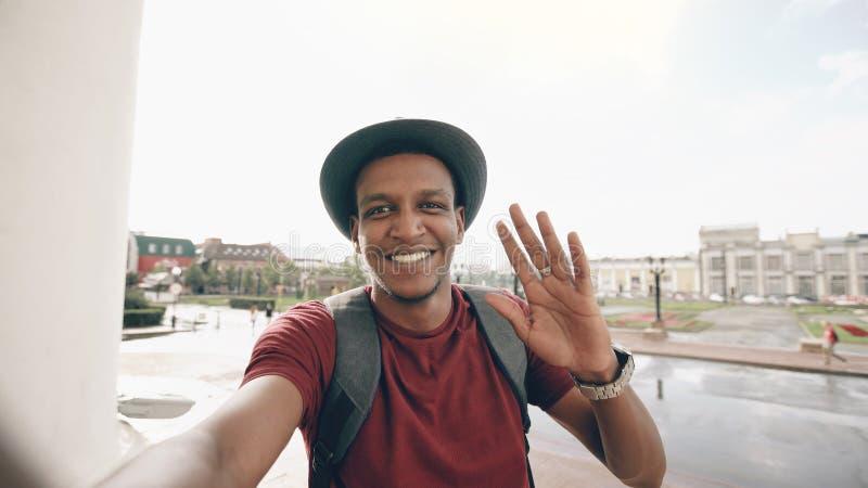 Hombre turístico afroamericano que tiene charla video en línea usando su cámara del smartphone mientras que viaja en Europa imágenes de archivo libres de regalías