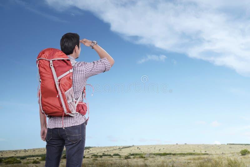 Hombre turístico asiático joven con la mochila que mira el cielo azul fotografía de archivo libre de regalías