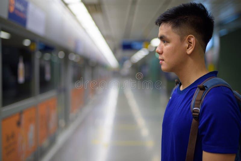 Hombre turístico asiático joven que espera el tren en la estación de metro foto de archivo