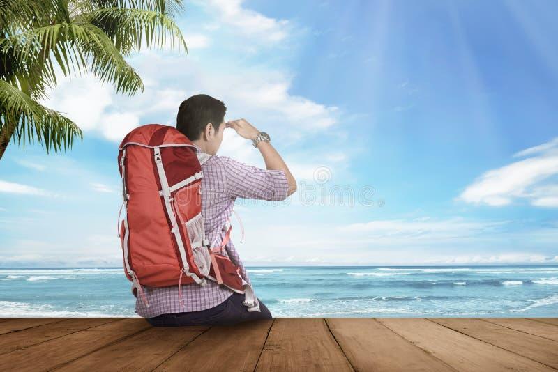 Hombre turístico asiático joven que sienta y que mira paisaje marino fotos de archivo libres de regalías