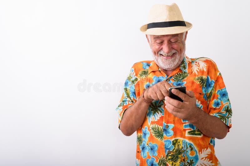 Hombre turístico barbudo mayor feliz que sonríe y que ríe nerviosamente mientras que usando el teléfono imagen de archivo