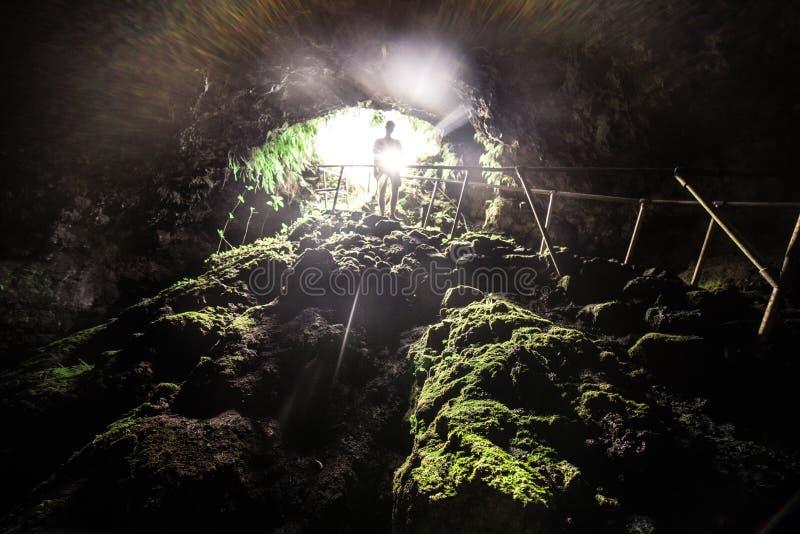 Hombre turístico explorar la cueva de la lava con la luz del flash en Maui, Hawaii imagenes de archivo