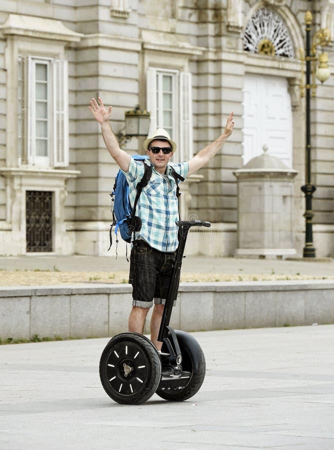 Hombre turístico feliz joven con el viaje de la ciudad del montar a caballo de la mochila segway conduciendo el palacio feliz y e imágenes de archivo libres de regalías