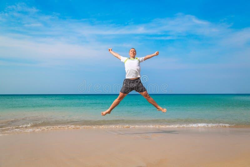 Hombre turístico feliz que salta en una playa tropical foto de archivo
