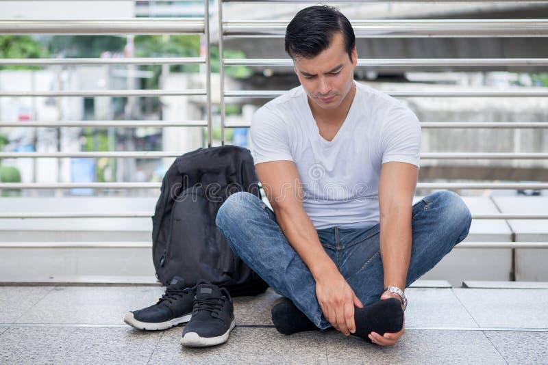 hombre turístico que se sienta en piso para sacar los zapatos que dan masajes a los pies que caminan mucho dolor del pie después  imagen de archivo