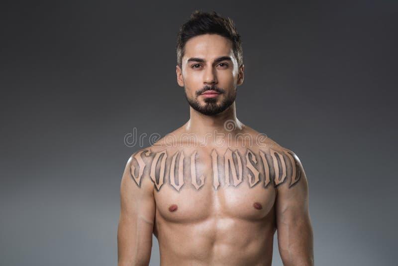 Hombre unclothed severo con el tatuaje foto de archivo