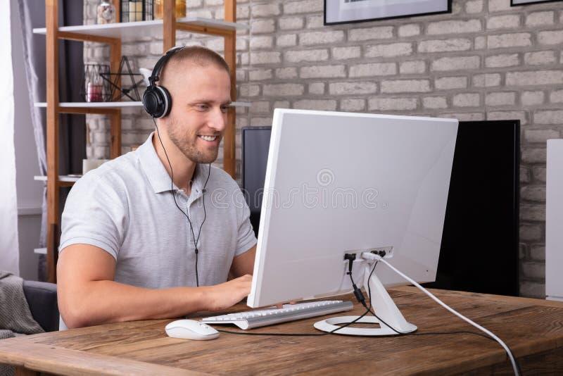 Hombre usando el auricular mientras que trabaja en el ordenador foto de archivo