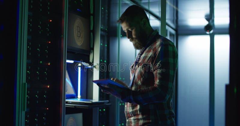 Hombre usando el ordenador portátil en granja minera en centro de datos foto de archivo