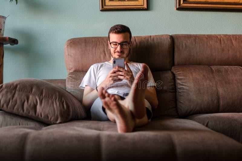 Hombre usando el teléfono móvil mientras que miente en el sofá en casa fotografía de archivo