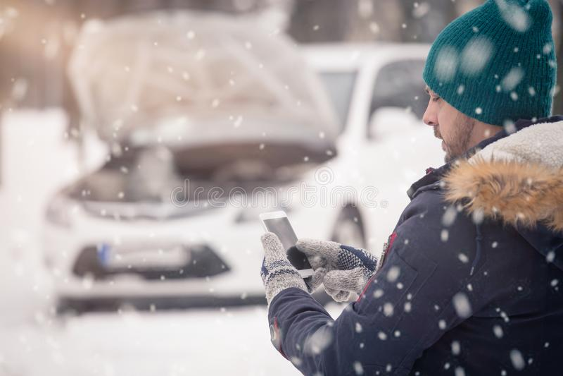 Hombre usando smartphone y pedir ayuda porque su coche es bro imagen de archivo libre de regalías